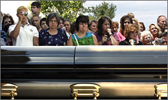 Members of Thomas Road Baptist Church and others watch as the coffin of the Rev. Jerry Falwell is moved into the church, in Lynchburg, Va., on Sunday.