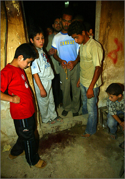 Palestinians inspect the blood left following an Israeli strike against the home of a Hamas leader Sunday in Gaza City.
