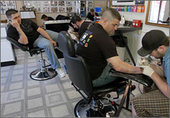 Pv2. Josh Bowser, right, and Sgt. Kyle Shaban of the 10th Mountain Division in Fort Drum, N.Y., get tattoos at the Empyre Tattoo shop in Carthage, N.Y.