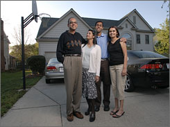 "Prashant Tungare, 55, far left, an immigrant from Mumbai, India, has lived ""the American Dream."" He stands with his wife, Madhuri, center left, his son Aneesh, 20, center right, and his daughter, Deepa, 26, outside of their Charlotte home."