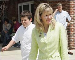 Sandee Winkelman leaves Monarch School in University Heights, Ohio with her autistic son, Jacob, on Monday.  A decision by the U.S. Supreme Court allows Sandee and her husband to sue the Parma, Ohio public school district over Jacob's special education needs without having to hire an attorney.
