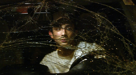A Lebanese youth is seen behind shattered glass of his car Monday night at the site where a bomb exploded just near the Russian cultural centre in an upmarket district of Beirut.