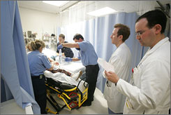 Seth Lessner, center, and Ian Schwartz treat a patient with chest pains.