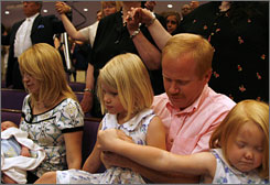 Steve Earnest holds daughters Katielyn, left, and Mary while he and his wife, June, pray during the Mother?s Day service at the North Cleveland Church of God.