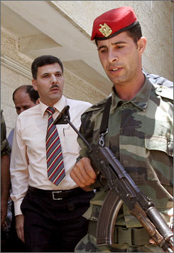 Palestinian Deputy Prime Minister Nasser Shaer, left, escorted by a Palestinian police officer, visits a hospital in the West Bank town of Ramallah in this August 2006 photo. Israeli troops in the West Bank arrested more than 30 senior Hamas members, including Shaer, Thursday morning.