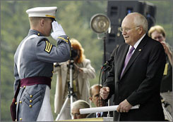 A graduating West Point cadet salutes Vice President Dick Cheney before receiving his diploma.