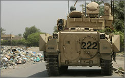 U.S. soldiers stop their armored vehicle to check on a body in Baghdad.
