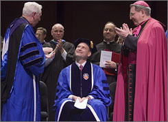 Supreme Court Justice Samuel Alito sits between Monsignor Robert Sheeran, left, and Archbishop John Myers, right, while receiving a standing ovation during Seton Hall University's School of Law Commencement Exercises in Newark, N.J. Friday. Alito received an Honorary Degree and was the Keynote Speaker.