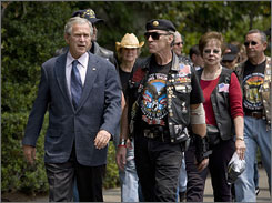 "President Bush walks with ""Rolling Thunder"" Executive Director Artie Muller, right front, and other members of the motorcycle group near the South Portico of the White House Sunday."