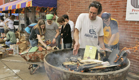 Tom Wayne lights books on fire at Prospero's Books in Kansas City, Mo., Sunday. The book store owner burned the books to protest the lack of reading in America.