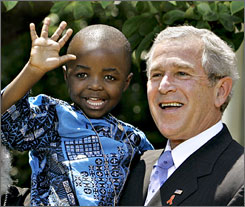 After speaking on his efforts to fight HIV/AIDS, President Bush, right, hoists 4-year-old Baron Mosima Loyiso Tantoh, whose mother is HIV positive, in the Rose Garden of the White House in Washington, D.C., Wednesday.
