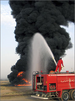 A firemen hoses down a burning oil pipeline May 24 after a bomb attack near the city of Kirkuk when an oil pipeline was destroyed after a roadside bomb attack.