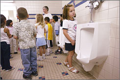 Kindergarteners tour the boys' bathroom on the first day of class at Columbia Elementary School in Wenatchee, Wash. However, at some schools students don't get to see the restroom nearly often enough, according to some urologists.