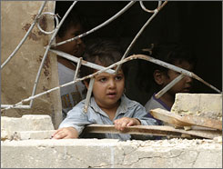 A child looks from the window of a damaged building that was turned into a makeshift refugee camp for displaced Sunni families in Fallujah. Most of those uprooted from their homes come from Baghdad and its surrounding districts, according to the agency.