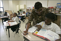 "Martin Luther King Charter School fifth-grade teacher Breeda Thompson, helps Brandon Bee, 12, during English class. Thompson, whose home was flooded during Hurricane Katrina, has made the move back to New Orleans and is trying to resettle her life. She says her students ""help me keep myself together."""