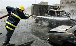 An Iraqi firefighter douses a blaze that swept over vehicles at the site of a car bomb in Baghdad's al-Talibiyah neighborhood.