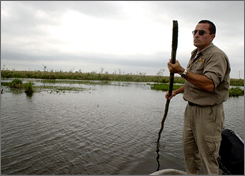 A man pushes his boat in the Esteros del Ibera, north of Argentina, near the area owned by U.S. businessman Douglas Tompkins, in this April 2007, file photo.