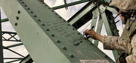 "A U.S. Marine writes on a beam of a bridge in western Fallujah, Iraq, where the bodies of two American contractors killed by militants were strung up in March 2004. An earlier message left by soldiers reads: ""This is for the Americans of Blackwater that were murdered here in 2004, Semper Fidelis 3/5."""