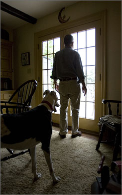 Charley Lloyd of New Holland, Pa., takes a look at the thunderstorm taking place outside as Tommy, an 8-year-old greyhound owned by Charley and his wife, Jane, stands behind him. Tommy takes an anti-anxiety drug to tame his phobia of thunderstorms.