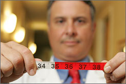 Dr. Louis Aronne, who is the current president of the North American Association for the Study of Obesity, holds up a measuring tape that indicates in red the waistline measurement past which women are considered to be at risk for obesity.