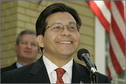 "U.S. Attorney General Alberto Gonzales smiles as he responds to a question on the Senate's no-confidence vote Monday. ""I am not focusing on what the Senate is doing,"" Gonzales said. Republicans blocked the vote Monday, turning back a symbolic Democratic effort to prod Gonzales from office."