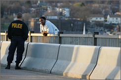 A police officer speaks with Brian Smith, right, as Smith is on the edge of the Commodore Barry Bridge, Wednesday, March 28,  near Chester, Pa.