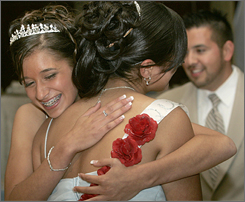 Quinceaneras Samantha Lynch, facing camera, hugs her best friend Daniela Muniz after removing the rose sash and presenting it to her friend as the next quinceaneras in line for the honor, May 26, in Katy, Texas.