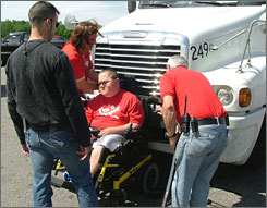 """Ben Carpenter, 21, of Kalamazoo, Mich., found himself stuck to the front grill of this semi truck in his motorized wheelchair, on June 6, 2007, authorities said. The young man, reportedly unhurt, was quoted by police as saying, """"It was quite a ride."""""""