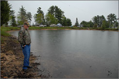 Ted Shalifor of the Ojibwa Recreation Area in Baraga, Mich., looks out over the campground marina that should be filled with docks and boats. Lake levels this year were so low the campground was unable to install the docks.