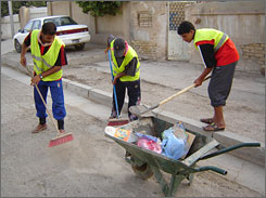 Sanitation workers, from left, Ammar Saddam, 25, Abdel Razzak Juma'a, 30 and Naeem Khalaf, 19, collect trash in a wheelbarrow off a neighborhood street in east Baghdad.