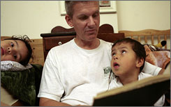 Bill Wilson reads to Tony, left and Bryan, right, before going to bed at their home in Washington, D.C. The number of single men who adopted children from foster care has more than doubled in the last decade, and more are also becoming foster parents.