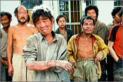 A group of slave laborers rescued from a brick kiln in Linfen, northern China's Shanxi province, in late May stand outside a police station. About 550 slave laborers have been freed from various brick kilns and mines in central China in the past month.