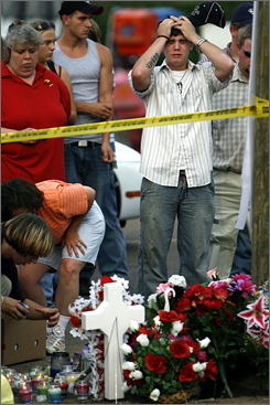 David Ferguson weeps while standing at a memorial in Selmer, Tenn., Sunday, a day after a drag-racing car careened into a crowd and killed six people.