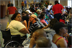Maria Gutierrez, in yellow, and hundreds of others wait to be seen at specialty clinics at Ben Taub General Hospital in Houston. Gutierrez was having her ankle checked after surgery.
