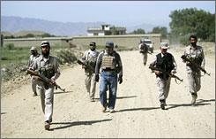 Project supervisor Ben Akari, center, a former New Zealand army commando, checks the progress of the road near Wazir.