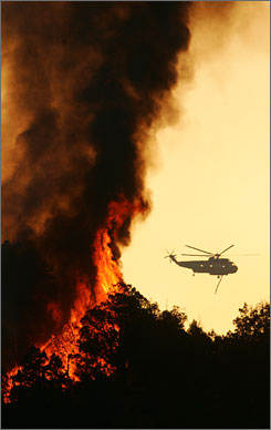 A helicopter passes by flames from a backfire while helping fight a wildfire near New Castle, Colo., Tuesday, June 19, 2007.