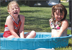 Madilynn Rogers, left, and Alyssa Ahlm react as they are sprayed with a hose in the hot sun on June 12 in Kingman, Ariz. Forecasters say the Desert Southwest can expect warmer that normal weather this summer.