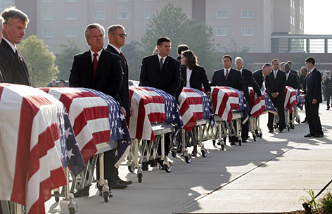 Pall bearers enter a memorial service with the flag-covered caskets of nine fire fighters in Charleston, S.C., Friday.