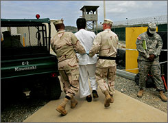U.S. military personnel escot a detainee on the grounds of the Guantanamo Bay detention facility at the U.S. Naval base in Cuba.