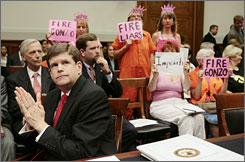 Deputy Attorney General Paul McNulty sits while during his testimony protesters hold signs calling for the firing of Attorney General Alberto Gonzales.
