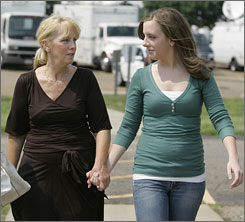 Patricia Porter, left, walks with her daughter Whitney Davis, after Porter answered media questions concerning her daughter, Jesse Davis, in Canton, Ohio.