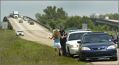 A Louisiana State Police trooper gives a ticket to a motorist on the west-bound lanes of the Atchafalaya Basin bridge in Henderson, La.