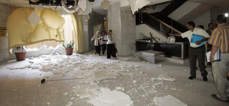 Iraqis inspect damage in the lobby of the high-rise Mansour Hotel in central Baghdad. A suicide bomber blew himself up in the crowded lobby of the hotel today, killing several people.