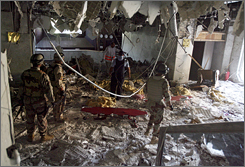 Iraqi soldiers step over bodies to inspect the rubble at the hotel.