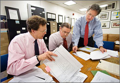 National Security Archive Executive Director Thomas Blanton, right; Senior Fellow and CIA expert John Prados, center; and Deputy Director Malcolm Byrne, left, examine internal reports released by the Central Intelligence Agency on Tuesday.