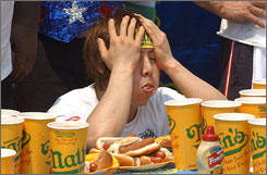 Takeru Kobayashi, from Nagano, Japan, recovers at the end of the Nathan's Famous hot dog eating contest in New York. Kobayashi who sets the world record for wolfing down dozens of hot dogs within minutes has suffered a severe jaw injury due to his rigorous training, making his next title uncertain.