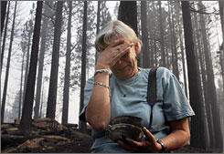 Missy Springer cries as she holds her grandmother's Royal Doulton china that she salvaged from the remains of her home that was completely destroyed by fire on Tuesday in Meyers, Calif.