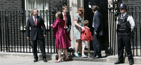 Britain's outgoing Prime Minister Tony Blair, left, accompanied by his wife Cherie, second left, and their children, Euan, third left, Kathryn, fourth left, Leo, second right, and Nicky, right, pose as a police officer looks on, as they leave the residence for the last time.