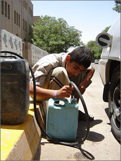 Black gold: Haidar Azhar, 12, fills cans, and coffers, for gas peddler Awad Fakhri. Fakhri pays a $25 bribe to get gas.