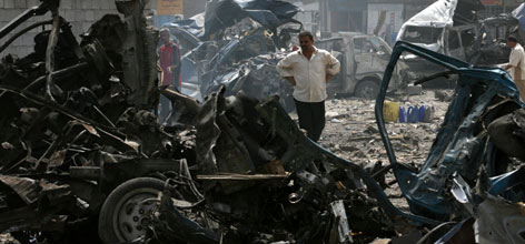 A man stands among destroyed vehicles at a bus station in the Baiyaa neighborhood in Baghdad, Thursday. A parked car bomb exploded in one of Baghdad's busy outdoor bus stations at rush hour Thursday, killing more than a dozen people and wounding at least 50, police said. Some 40 minibuses were incinerated in the explosion.